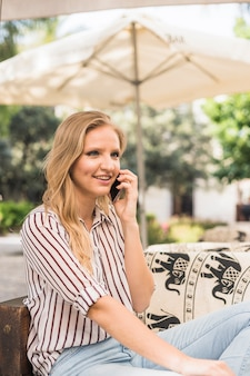 Glimlachende jonge vrouw die openlucht het spreken op mobiele telefoon zitten