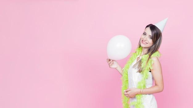 Glimlachende jonge vrouw die partijhoed draagt die witte ballon houdt