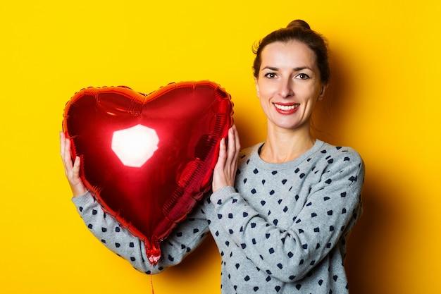 Glimlachende jonge vrouw die rode hartvormige luchtballon op gele achtergrond houdt.