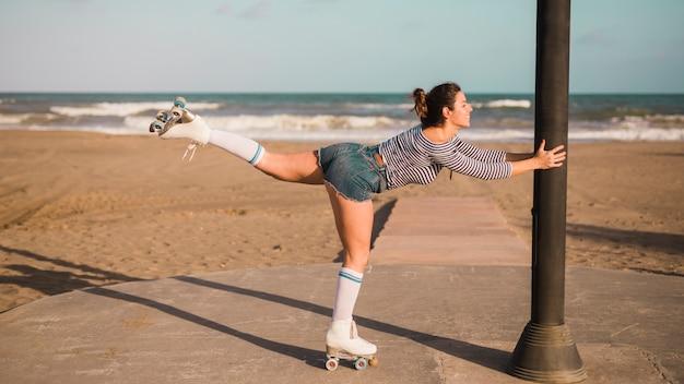 Glimlachende jonge vrouw die rolschaats dragen die op één been bij strand in evenwicht brengen