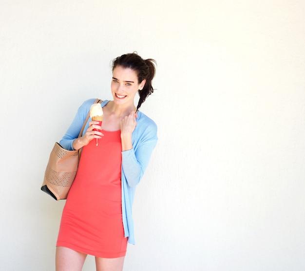 Glimlachende jonge vrouw die roomijs eet