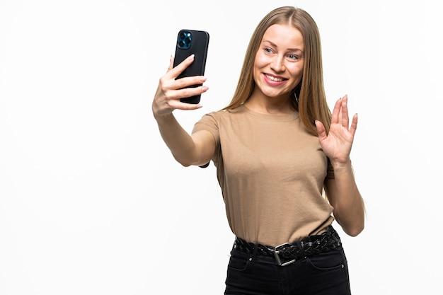 Glimlachende jonge vrouw die selfie foto maakt terwijl ze zwaait met palm geïsoleerd op een wit oppervlak