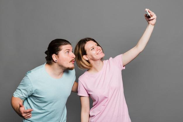 Glimlachende jonge vrouw die selfie met haar vriend tegen grijze achtergrond nemen