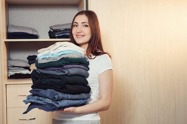 Glimlachende jonge vrouw die staat met een hoop gevouwen kleding in handen glimlachend naar de camera, kopieer ruimte