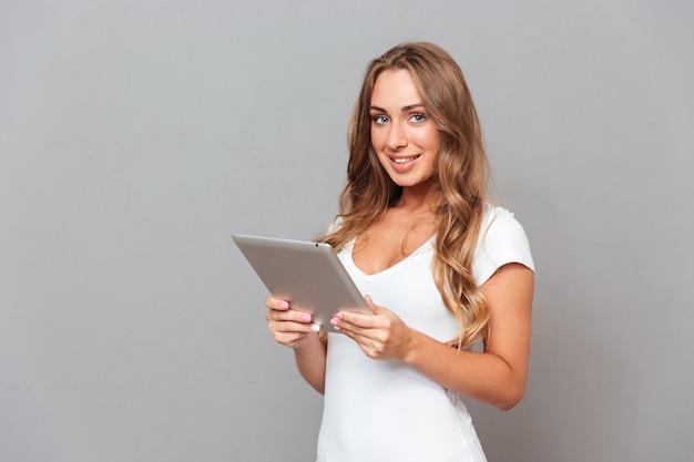 Glimlachende jonge vrouw die tabletcomputer met behulp van en voorzijde bekijken die op een grijze muur wordt geïsoleerd