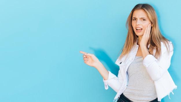 Glimlachende jonge vrouw die tandpijn heeft die vinger op blauwe achtergrond richt