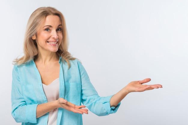 Glimlachende jonge vrouw die tegen witte achtergrond voorstellen