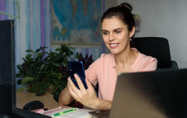 Glimlachende jonge vrouw die thuis werkt