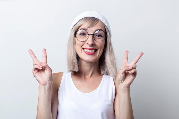 Glimlachende jonge vrouw die twee vingers een overwinningsteken op een lichte achtergrond toont.