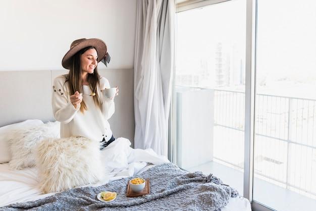 Glimlachende jonge vrouw die van het gezonde ontbijt op bed in de ochtend geniet