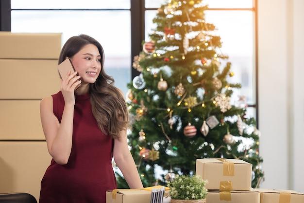 Glimlachende jonge vrouw die van huis werkt en op smartphone spreekt