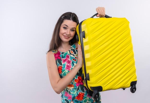 Glimlachende jonge vrouw die veelkleurige kleding draagt die een mobiele zak op witte muur houdt