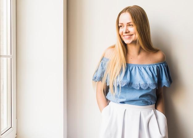 Glimlachende jonge vrouw die venster bekijkt