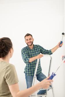 Glimlachende jonge vrouw die verfroller op de muur veegt terwijl ze kamer schildert met vriendje