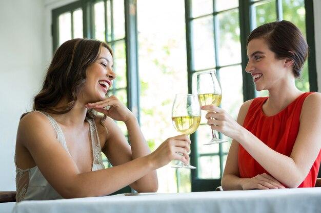 Glimlachende jonge vrouw die wijnglazen in restaurant roostert