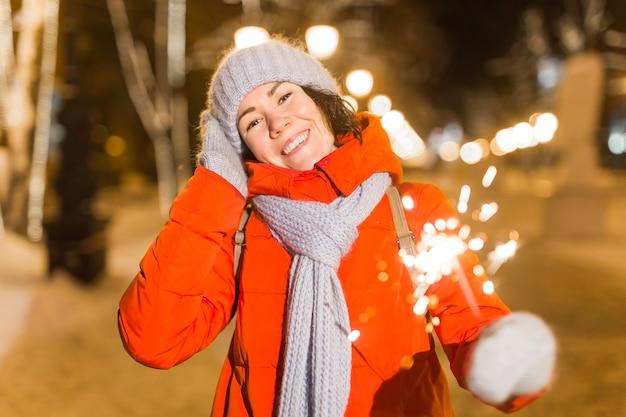 Glimlachende jonge vrouw die wintergebreide kleding draagt die sterretje buiten over sneeuwachtergrond houdt