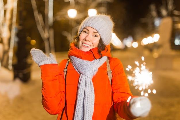 Glimlachende jonge vrouw die wintergebreide kleding draagt die sterretje in openlucht over sneeuwachtergrond houdt. kerstvakantie.