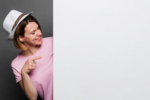 Glimlachende jonge vrouw die witte hoed draagt die vinger richt naar witte kaart