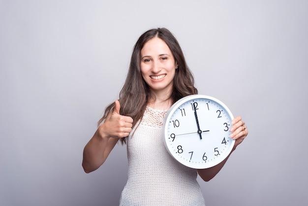 Glimlachende jonge vrouw die witte klok houdt en duim toont.