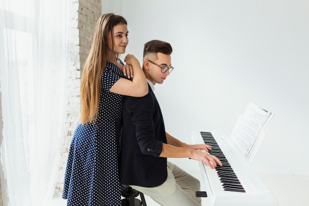 Glimlachende jonge vrouw die zich achter de man bevindt die de piano speelt