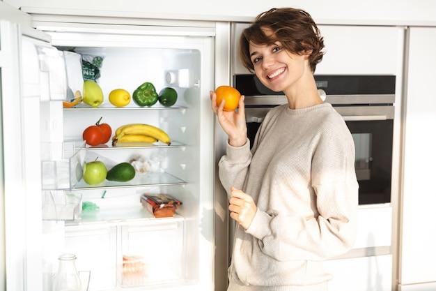 Glimlachende jonge vrouw die zich bij de koelkast bevindt, die sinaasappel houdt