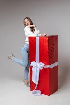 Glimlachende jonge vrouw die zich dichtbij grote rode giftdoos bevindt, die op grijze muur wordt geïsoleerd