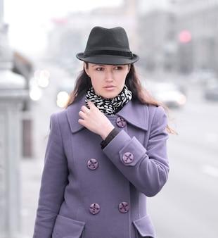 Glimlachende jonge vrouw die zich op straat in stad bevindt.