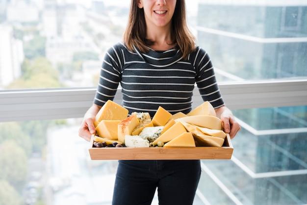 Glimlachende jonge vrouw die zich voor de kaas van de vensterholding in houten dienblad bevindt