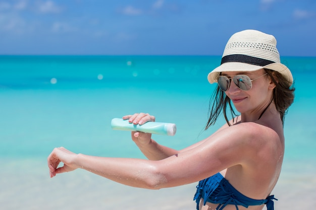 Glimlachende jonge vrouw die zonroom op strand toepast