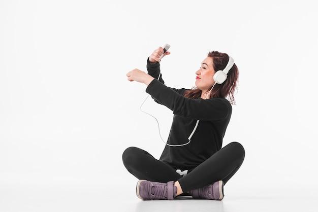 Glimlachende jonge vrouw het luisteren muziek op mp3 speler