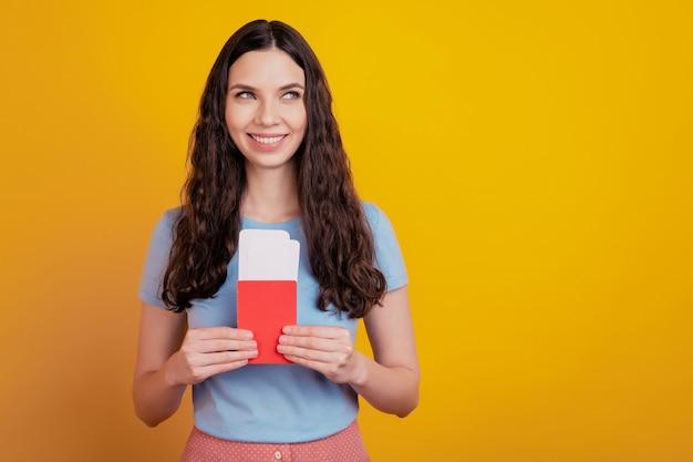 Glimlachende jonge vrouw houdt paspoort tickets instapkaart kijken lege ruimte geïsoleerd op felgele kleur muur achtergrond