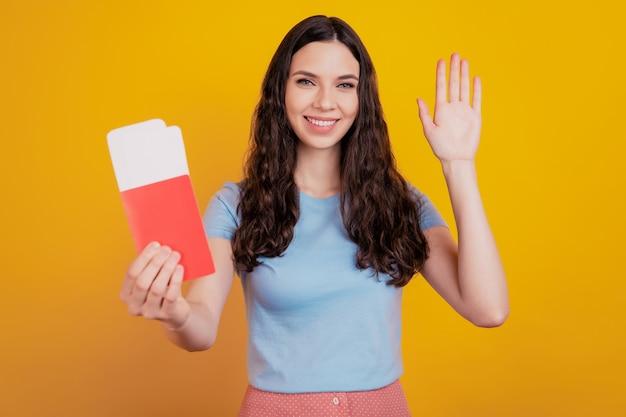 Glimlachende jonge vrouw houdt paspoort tickets instapkaart zwaaiende hand hallo geïsoleerd op felgele kleur muur achtergrond