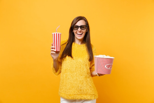Glimlachende jonge vrouw in 3d imax-bril kijken naar filmfilm, met emmer popcorn, plastic beker cola of frisdrank geïsoleerd op gele achtergrond. mensen oprechte emoties in de bioscoop, lifestyle concept.