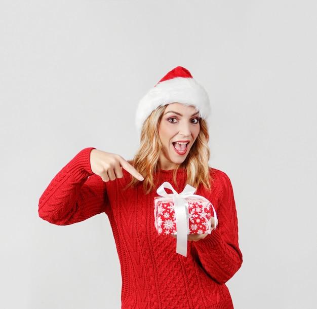Glimlachende jonge vrouw in aanwezige de holding van de santahoed