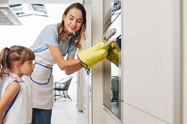 Glimlachende jonge vrouw in beschermende kokende wanten die oven openen om bijna gebakken cake aan dochter te tonen