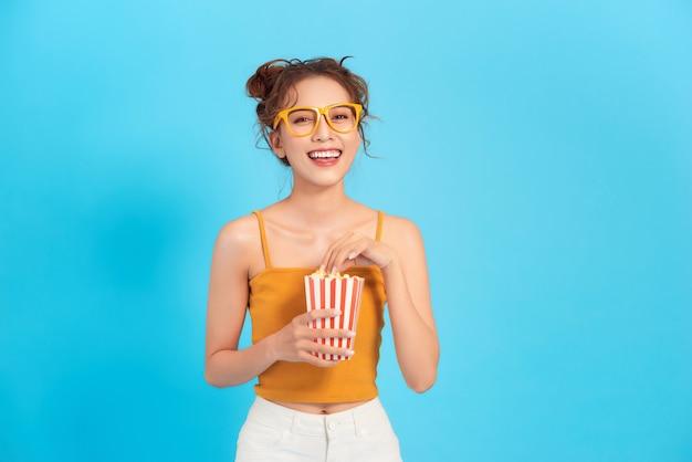 Glimlachende jonge vrouw in casual zomerkleren, houd emmer popcorn geïsoleerd op blauwe achtergrond.
