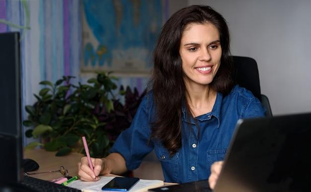Glimlachende jonge vrouw in denimoverhemd dat van huis met laptop werkt