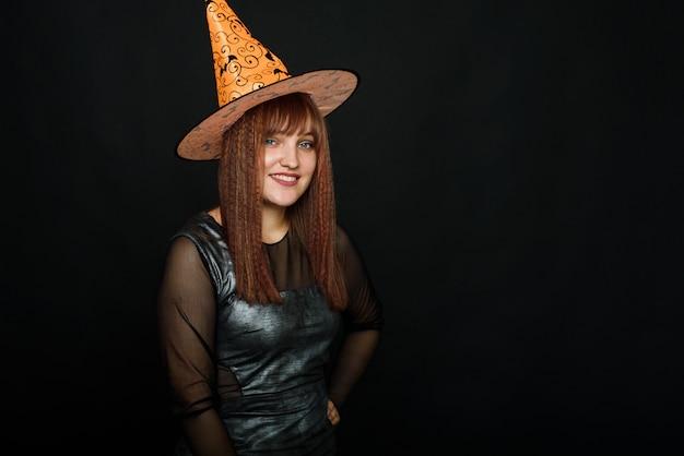 Glimlachende jonge vrouw in een heksenkostuum op zwarte achtergrond