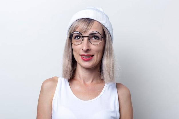 Glimlachende jonge vrouw in een witte hoed en bril op een lichte achtergrond.
