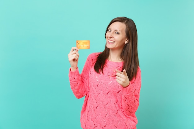 Glimlachende jonge vrouw in gebreide roze trui wijzende wijsvinger op camera, creditcard in de hand houden geïsoleerd op blauwe muur achtergrond studio portret. mensen levensstijl concept. bespotten kopie ruimte.