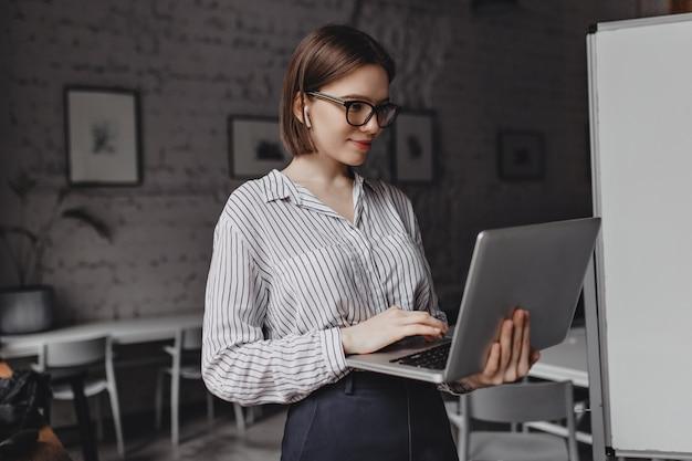 Glimlachende jonge vrouw in gestreepte blouse en zwart-omrande bril kijkt laptop scherm op achtergrond van wit bord.
