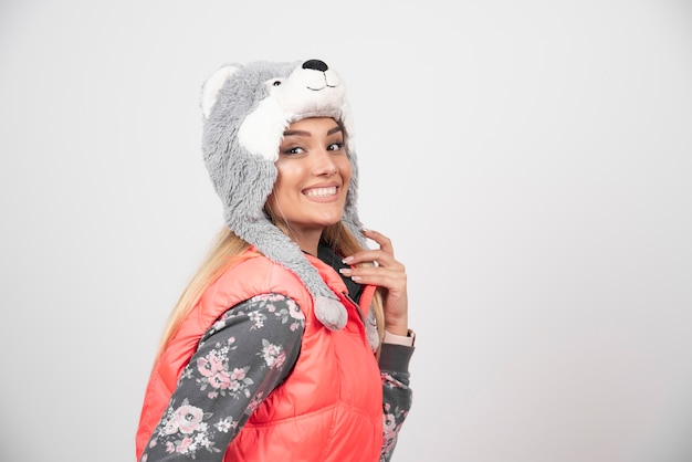 Glimlachende jonge vrouw in grappige hoed op een witte muur