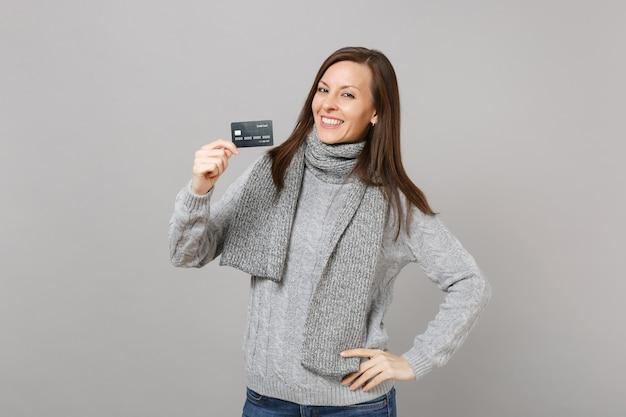 Glimlachende jonge vrouw in grijze trui, sjaal houd creditcard geïsoleerd op grijze muur achtergrond in studio. gezonde mode levensstijl mensen oprechte emoties, koude seizoen concept. bespotten kopie ruimte.