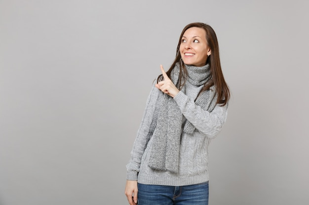Glimlachende jonge vrouw in grijze trui, sjaal opzoeken, wijzende wijsvinger opzij geïsoleerd op grijze muur achtergrond. gezonde mode levensstijl mensen emoties, koude seizoen concept. bespotten kopie ruimte.