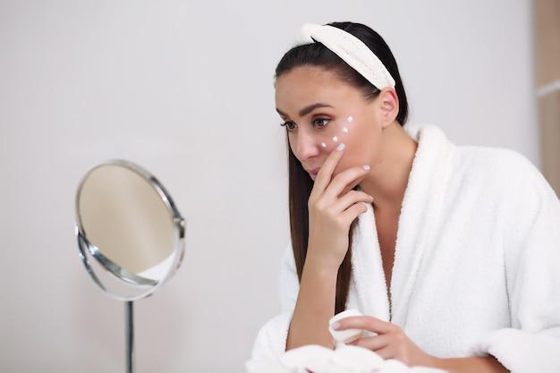 Glimlachende jonge vrouw in haarband wat betreft haar gezicht en thuis op zoek naar spiegel
