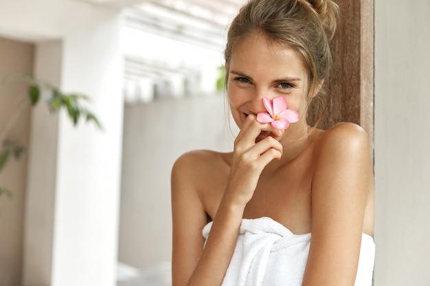Glimlachende jonge vrouw in handdoek