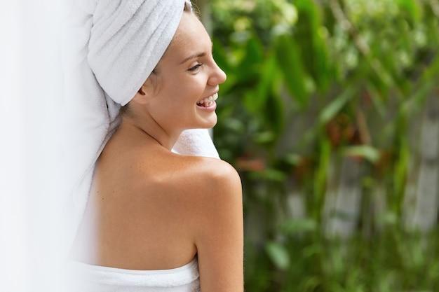 Glimlachende jonge vrouw in handdoeken