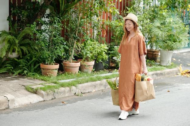 Glimlachende jonge vrouw in hoed en linnen jurk die naar huis loopt na het winkelen op de lokale markt
