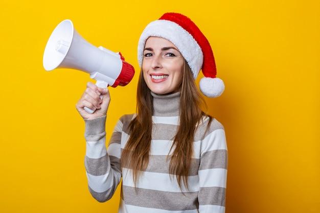 Glimlachende jonge vrouw in kerstman hoed met een megafoon op een gele achtergrond.
