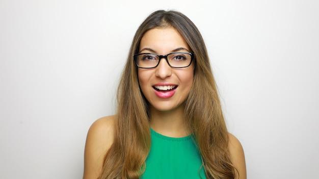 Glimlachende jonge vrouw in oogglazen poseren